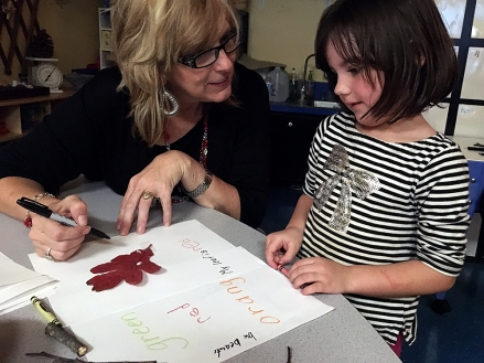 Teacher Jana Dunlap works with Grace Marder, 4, to come up with adjectives to describe a leaf the child found on a nature walk outside the Early Childhood Center in Muskogee, Oklahoma. Photo: Lillian Mongeau. Photo: The Hechinger Report