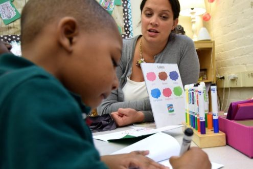 Boston Public Schools preschool teacher Mary Bolt watches Jason DePina Jr., 5, draw a picture of Batman for his book about superheroes in the classroom's writing section. Photo by Lillian Mongeau/Hechinger Report