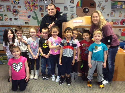 A preschool class at Little People's College that engages in community partnerships with local police.